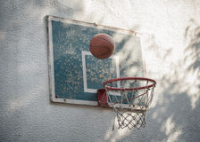 Ball basketball going through rustic old hoop with backboard Royalty Free Stock Photo