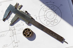 Ball bearing and caliper on the background of drawings Stock Photos
