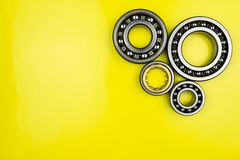 Ball bearing lying on a yellow background with copy space on the left side. Flat view from above. royalty free stock photos