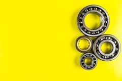 Ball bearing lying on a yellow background with copy space on the left side. Flat view from above. royalty free stock image