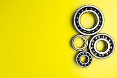 Ball bearing lying on a yellow background with copy space on the left side. Flat view from above. stock photo