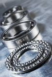 Ball-bearings concept in bluish. Four ball-bearings in a row against stainless-steel royalty free stock photography