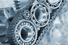 Ball bearings and engineering parts. Ball-bearings, gears and chains, engineering concept in blue royalty free stock photography