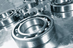 Ball-bearings and gear wheels. Set against titanium background, and in a blue toning concept stock image