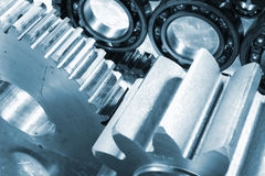 Ball-bearings, gears and chains. Engineering parts, ball-bearings, gears and cogwheels driven by timing-chain, titanium and steel, duplex blue toning concept royalty free stock photo