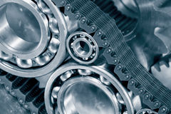 Ball-bearings, gears and chains. Engineering parts, ball-bearings, gears and cogwheels driven by timing-chain, titanium and steel, duplex blue toning concept royalty free stock images