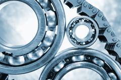 Ball-bearings, gears in close-ups. Engineering parts, ball-bearings, gears and cogwheels driven by timing-chain, titanium and steel, duplex blue toning concept stock image