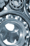 Ball-bearings, gears in close-ups. Engineering parts, ball-bearings, gears and cogwheels driven by timing-chain, titanium and steel, duplex blue toning concept royalty free stock photography