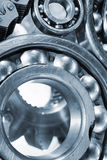 Ball-bearings and gears in close-ups. Titanium and steel parts, ball-bearings and gears in a metal blue toning concept royalty free stock photography