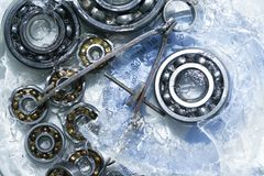 Ball Bearings In Ice. Machinery concept. Closeup set of ball bearings under frozen water royalty free stock images