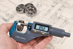 Ball bearings measurement. Micrometer screw gauge in human hand. Digital display on precise measuring tool. Technical drawing and group of metal parts on royalty free stock images