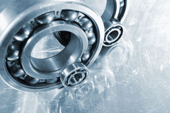 Ball-bearings mirrored in steel. Ball-bearings, steel parts, mirrored in a steel background, metal blue toning concept stock photo