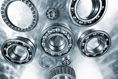 Ball-bearings, titanium and steel. Differant ball-bearings, gears, in a super-wide perspective, set against a titanium background stock image