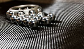 Ball bearings and wheel bearing on carbon fiber cloth 2. Loose ball bearings in front of an automotive wheel bearing on carbon fiber cloth royalty free stock photo