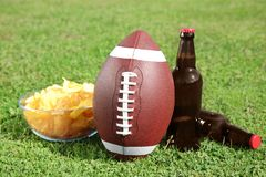 Ball with beverage and chips on fresh green. Field grass. American football match royalty free stock photo