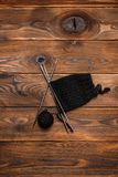 Ball of black knitting thread and knitting pattern on a wooden background. A ball of black knitting thread and knitting pattern on a wooden background stock photography