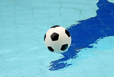 Ball in blue pool water background Stock Photography