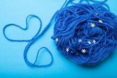 A ball of blue thread for knitting and a heart laid out of a thread royalty free stock images