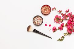 Ball blush rouge and face powder, makeup brush, spring pink flowers on light background top view flat lay copy space. Different. Makeup cosmetic. Beauty fashion royalty free stock photo