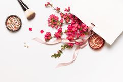 Ball blush rouge and face powder, makeup brush, spring pink flowers in white gift package on light background top view flat lay. Different makeup cosmetic royalty free stock photo