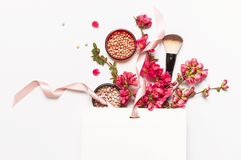 Ball blush rouge and face powder, makeup brush, spring pink flowers in white gift package on light background top view flat lay. Different makeup cosmetic royalty free stock image