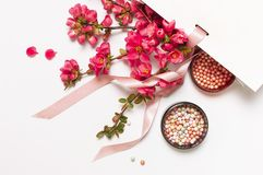 Ball blush rouge and face powder, makeup brush, spring pink flowers in white gift package on light background top view flat lay. Different makeup cosmetic stock photography