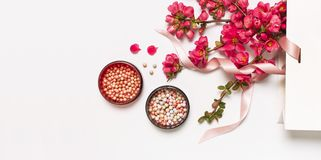 Ball blush rouge and face powder, makeup brush, spring pink flowers in white gift package on light background top view flat lay. Different makeup cosmetic stock photo