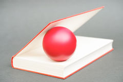 Ball in a book Stock Images