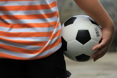 A ball and a boy. A soccer ball is hold by a little boy who want to go outside to play it Stock Image