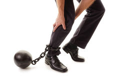 Ball and chain. Restraining a businessman as he tries to walk concept for business burden, willpower and determination Stock Image