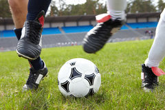 Ball chase. Horizontal image of soccer ball on the field with footballers legs near by Stock Photo