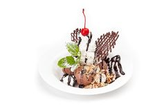 The ball of chocolate ice cream and the shaken up cream. Powdered with icing sugar on a white dish, are decorated by berries and nuts, watered with chockolate stock photography