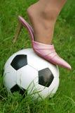 Ball control. Pink stiletto on football stock image