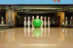 Ball crashing into pins. Photo of green ball crashing into pins Stock Photography
