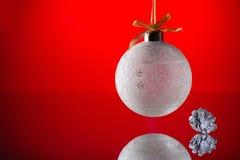 Ball der weißen Weihnacht und silberne Kiefern-Kegel auf Spiegel Lizenzfreies Stockbild