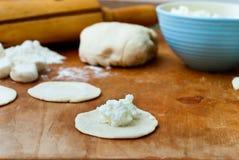 Ball des Teigs und der Stückchen gerollter Tortillas für Mehlklöße mit Hüttenkäse auf einem hölzernen Brett der Küche Stockbilder