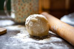 a ball of dough sprinkled with flour, rolling pin and flower duster royalty free stock photos