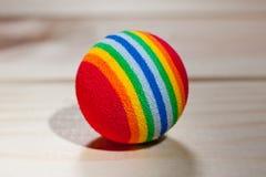 Ball für die Haustiere rot mit farbigen Streifen, elastisch auf einem hölzernen Hintergrund stockfoto