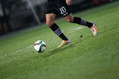 Ball and a feet of a soccer player Stock Photos