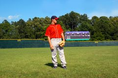 Ball Field Warmup. Young man stands looking at infield waiting for warmup.  Red uniform top with grey pants.  Scoreboard in rear of picture Stock Photography