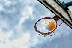 The ball flies into the basketball basket against a cloudy sky royalty free stock photography