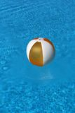 Ball floating in blue water. Blow up beach ball floating in blue sea or swimming pool stock photos