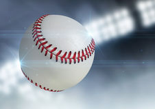 Ball Flying Through The Air. A regular baseball ball flying through the air on an indoor stadium background during the night stock photo