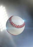 Ball Flying Through The Air. A regular baseball ball flying through the air on an a outdoor stadium background during the night royalty free stock photos