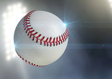 Ball Flying Through The Air. A regular baseball ball flying through the air on an a outdoor stadium background during the night stock photos