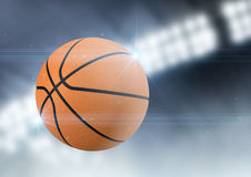 Ball Flying Through The Air. A regular basketball flying through the air on an indoor stadium background during the night royalty free stock photography