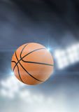 Ball Flying Through The Air. A regular basketball flying through the air on an indoor stadium background during the night stock photo