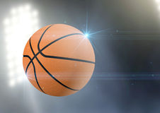 Ball Flying Through The Air. A regular basketball flying through the air on an a outdoor stadium background during the night stock images