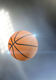 Ball Flying Through The Air. A regular basketball flying through the air on an a outdoor stadium background during the night stock photos