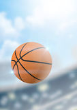 Ball Flying Through The Air. A regular basketball flying through the air on a stadium background during the daytime stock photo